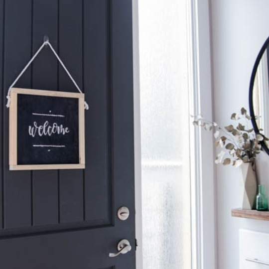 Wooden Chalkboard Sign On A Dark Front Door With White Walls
