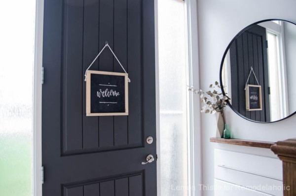 Wooden Chalkboard Welcome Sign Hanging On Front Door, With Circle Mirror In Entryway